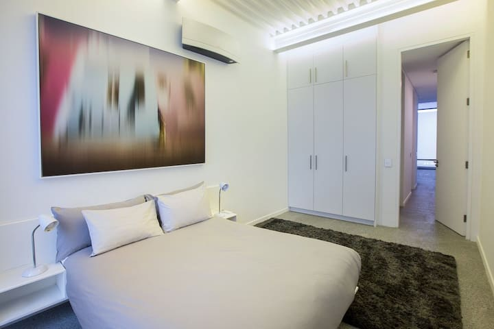 This is the guest bedroom. Soft rug. Pocket-springs, premium Queen-size mattress, premium linens, large floor to ceiling built-in cupboards, LED lighting, bedside plugs and reading lights.