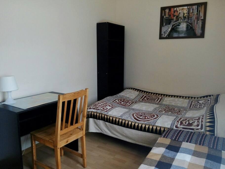 Комната с двумя кроватями (двуспальная и односпальная). А так же стол, встроенный шкаф и небольшой стеллаж.