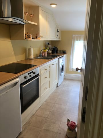 Separate kitchen area with all essential appliances such as fridge, toaster, kettle and oven.