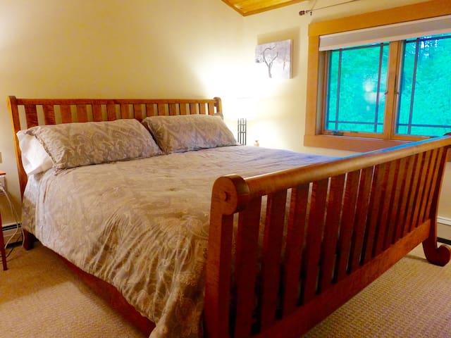 King bedroom, second floor, custom tiger wood Vermont made bed.