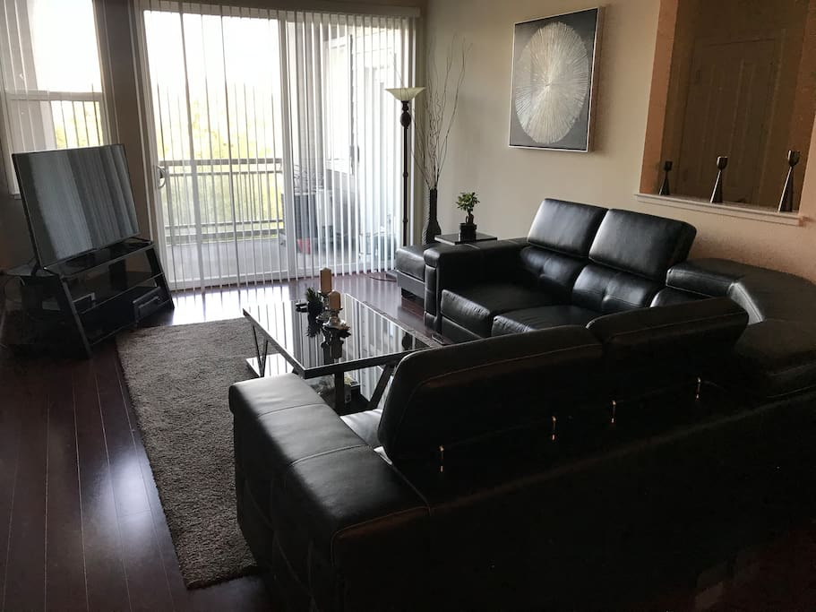 Living room with L-shaped leather sofa, 5.1 sound system, flat screen TV, and access to patio