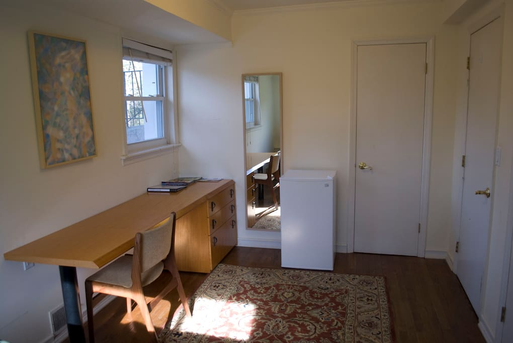 This guest room has a long desk, plus a small room fridge.