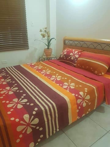Spacious bedroom with AC and a queen size bed plus wardrobe and hangers. The bathroom is located as a separate room off the bedroom equipped with a shower, sink and toilet.