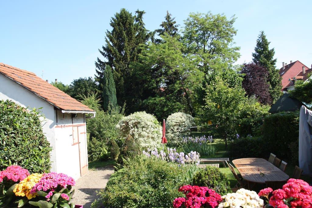 Le jardin fleuri, harmonieux et accueillant avec sa grande table en bois et son parasol ...