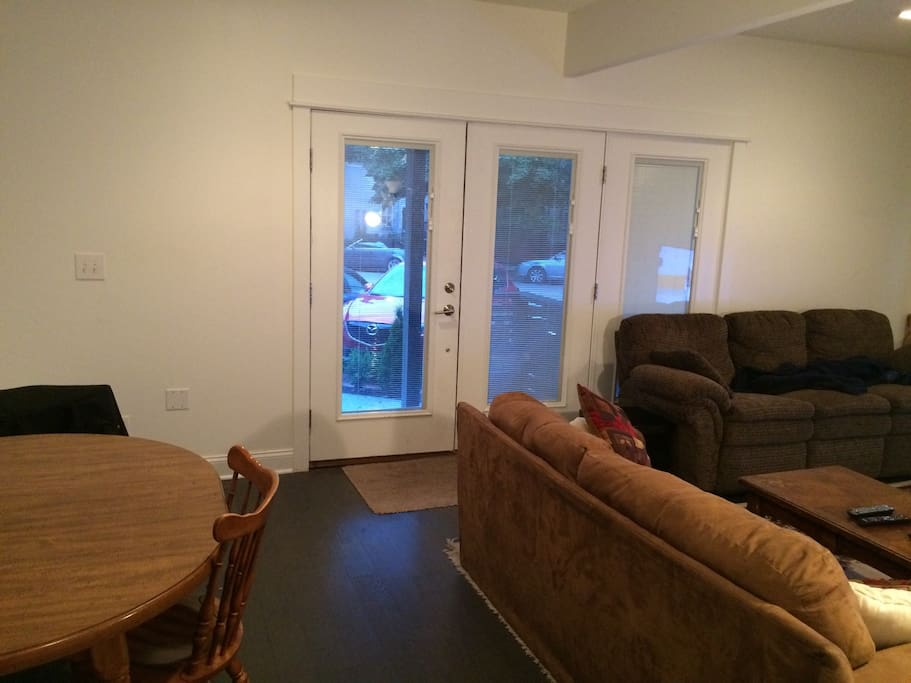 """Great room: living/dining room with 2 couches, love seat, 55"""" LED SMART TV, sound bar and kitchen table eating area. Has double doors for nice summer days."""