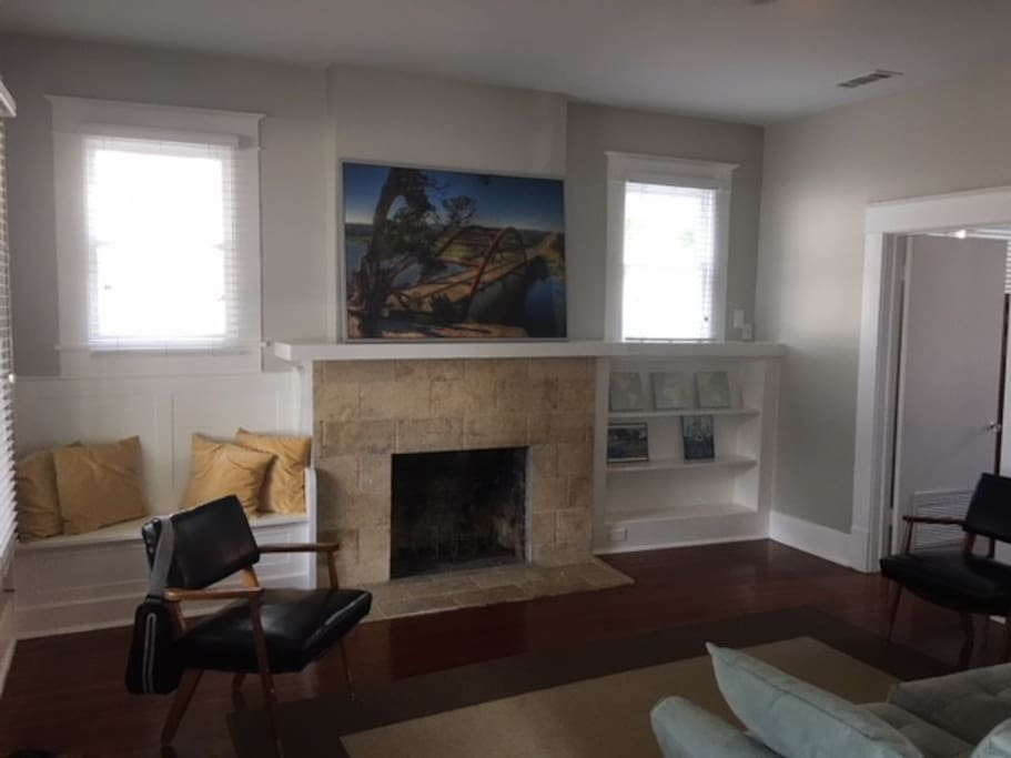 Enjoy the warm and inviting living room with the travertine fireplace, built in reading benches and dark hardwood floors