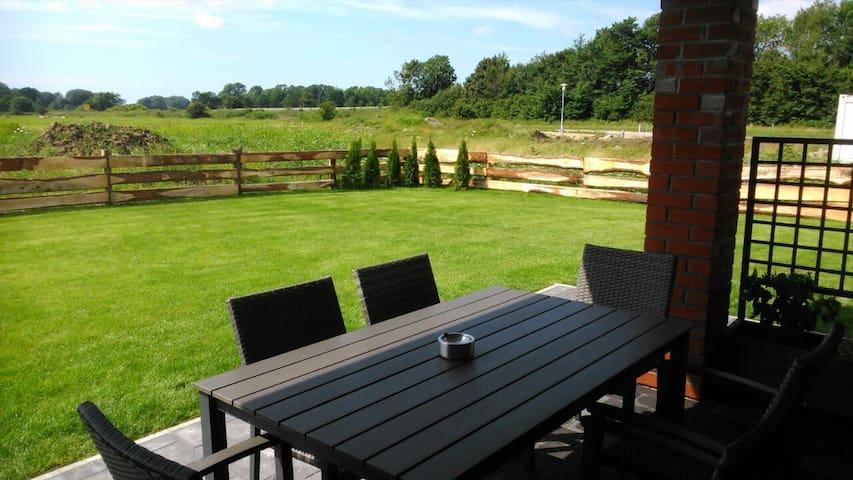 Überdachte Terrasse mit Garten eingezäunt