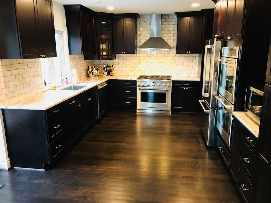 The main kitchen is available to guests and includes three ovens, a microwave, dishwasher, and gas-top stove with hood.