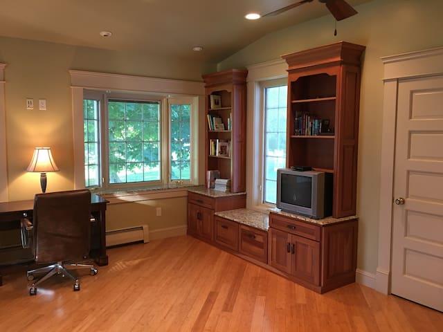 The office bedroom features several built-ins and a small satellite TV.