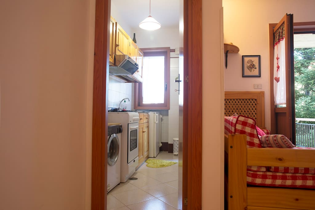 Cucina con angola cottura, lavatrice, frigorifero e con 2 finestre una comunica con la terrazza