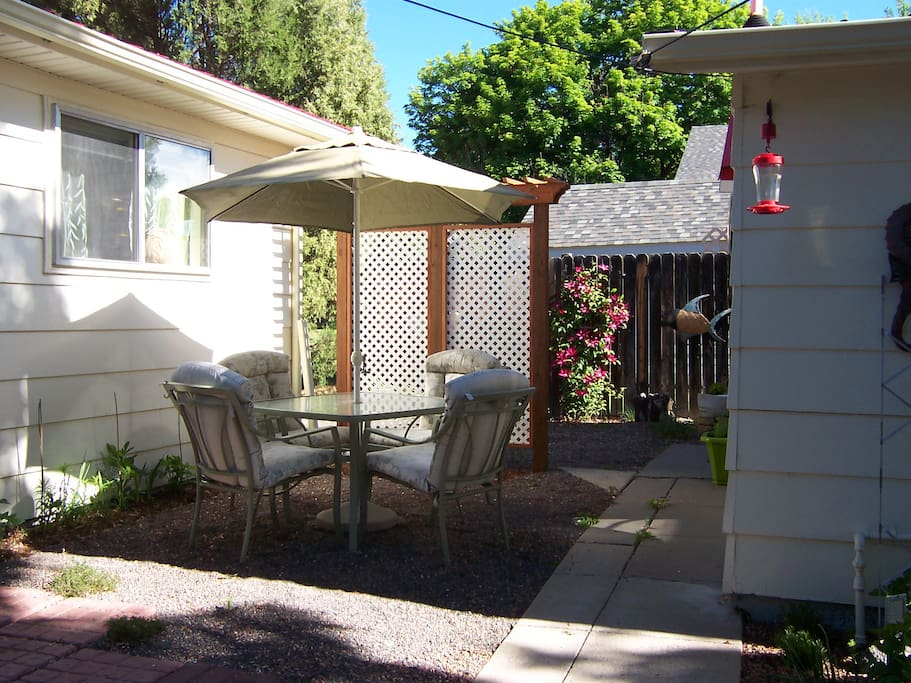 Patio dining with view of garden and back yard
