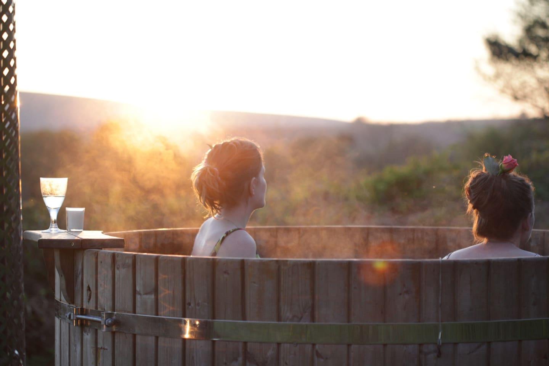 Shepherds huts private hot tub at sun set