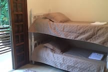 Quarto #2 com uma cama de solteiro, uma beliche e varanda