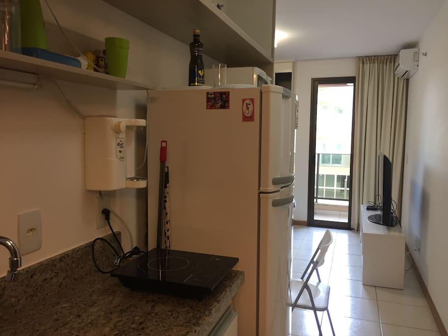Cozinha com geladeira/freezer, fogão elétrico de 01 boca, microondas, filtro de água, utensílios de cozinha (prato, talheres, copos, canecas e uma frigideira). Cozinha típica de Flat para refeições simples.