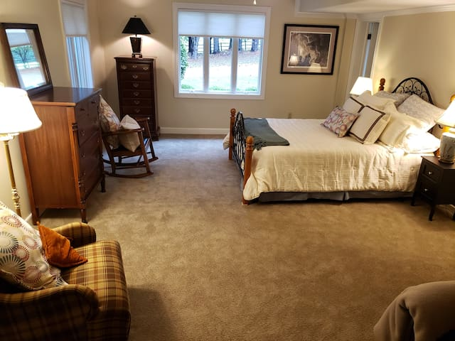 Bedroom with queen bed, two standard pillows, desk ,dresser and comfortalbe chairs for reading.