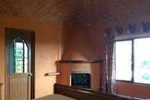Habitación con cama matrimonial y baño contiguo en segundo piso