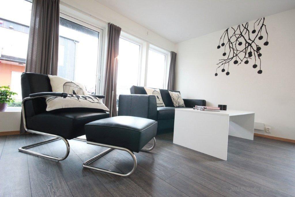 Romslig stue med sofagruppe, kjøkkengruppe og åpen kjøkkenløsning.