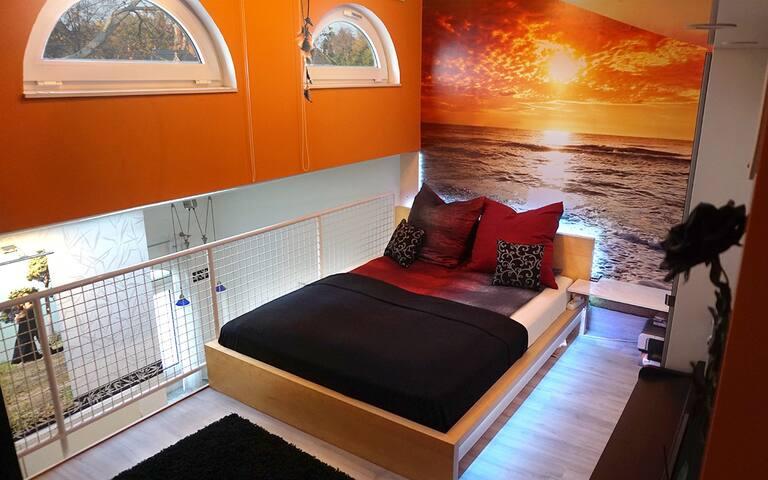 Schlafbereich mit gemütlichem Sonnenuntergang und indirekter Beleuchtung / Sleeping area with cozy sunset and indirect lighting