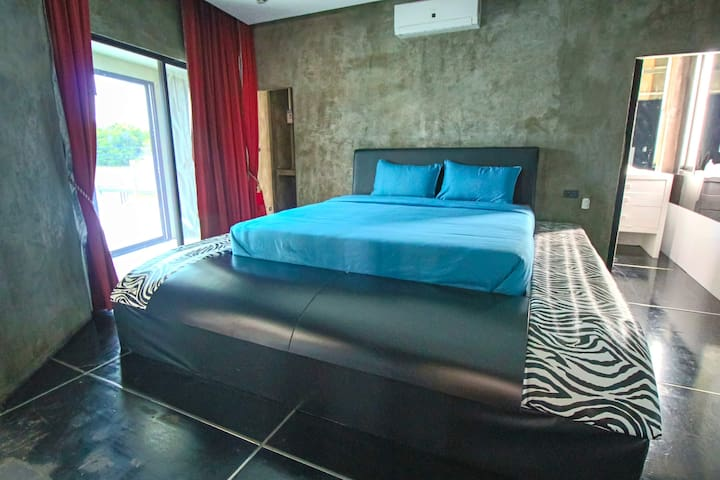 Upstairs bedroom with king size bed and air conditioner