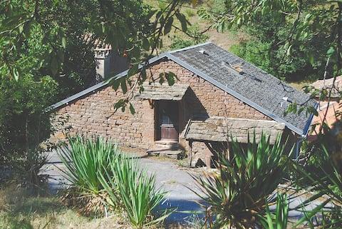 Petite maison en pierre rouge en pleine nature