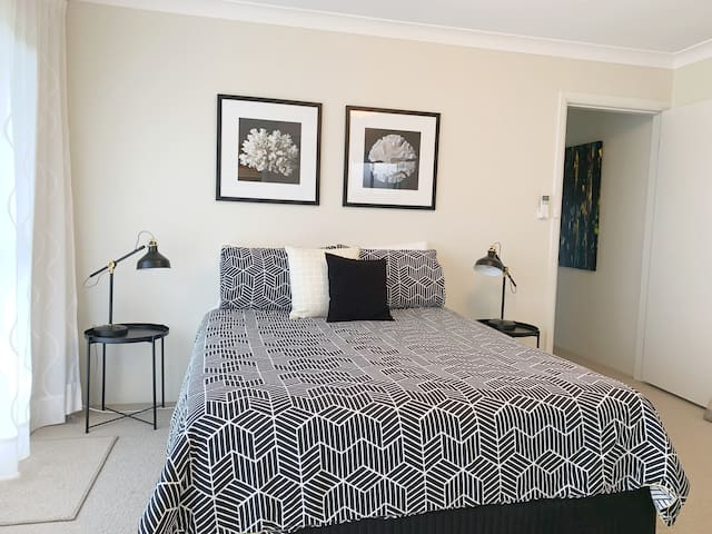Ensuite bedroom with queen size bed opens to the lower deck and yard