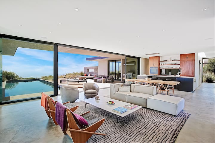 Floor-to-ceiling glass doors open up to mountain and ocean views in the contemporary living area.