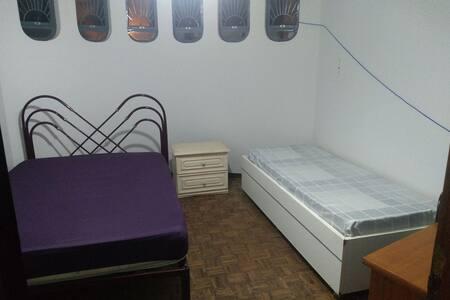 Quarto individual contendo cama e pequeno armário