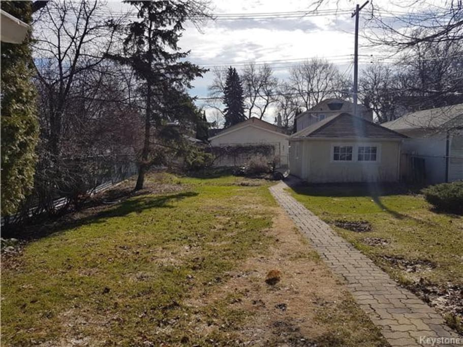 Fenced in back yard with single detached garage. There is also a small rock garden in the back.