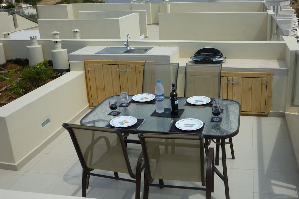 Dining area on private roof terrace, including refrigerator in cupboard