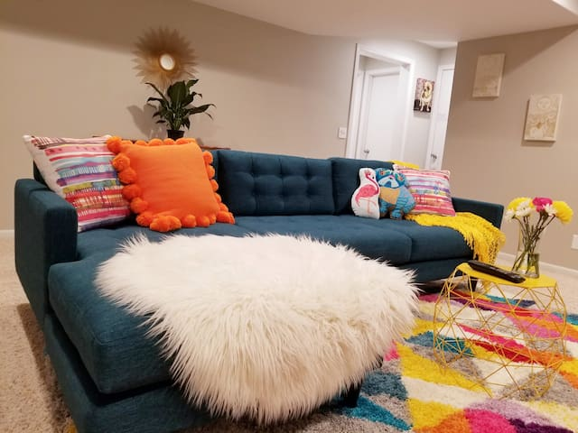This bold, bright and sizable living room is included in the luxury suite. A spacious mid-century modern sectional,  loaded with fun and comfy pillows, provides the perfect setting to enjoy some Netflix or Hulu Live TV.