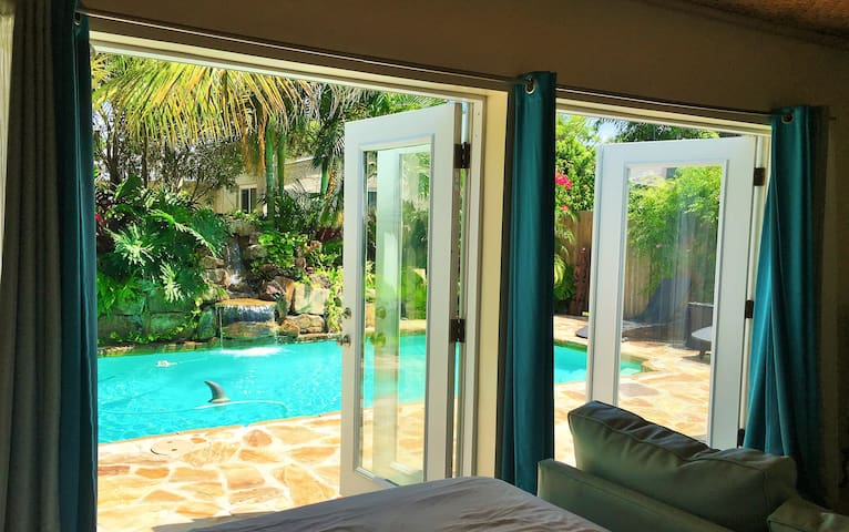 View from master bedroom with two sets of french doors that open to the private pool with waterfall.