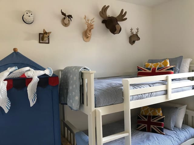 Children's bunk room with 4 single beds .