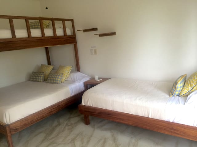 """The Third bedroom we call the """"Bunk Room"""". It sleeps 4 people with one double bed and two singles. This room also has a sliding door leading out to the pool and the garden, as well as a large closet space."""