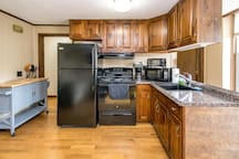 Brand new black fridge, stove, vent fan, and sink