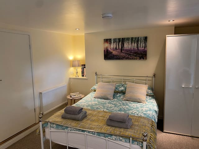 Bedroom space comprising double bed and single bed, with double wardrobe and chest of drawers
