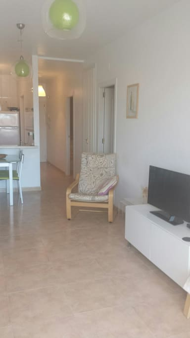 Large TV with DVD player and suitable furniture for resting or eating.