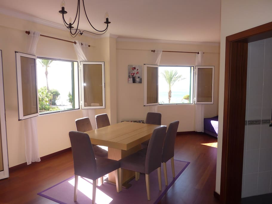 Spacious sunny lounge and dining area with two windows with ocean views