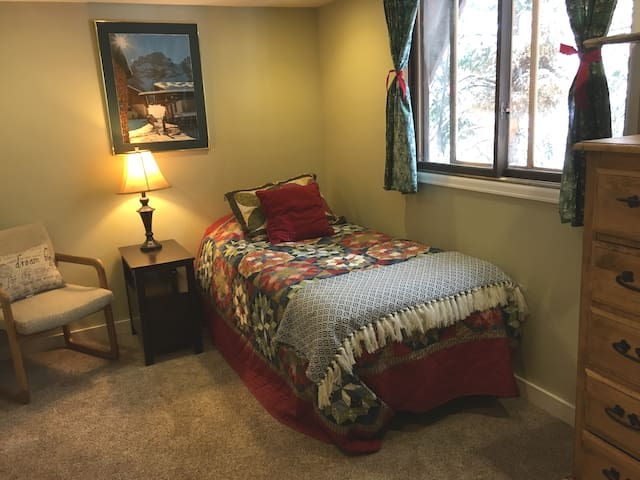 Secondary upstairs bedroom with full bed and views of the forest