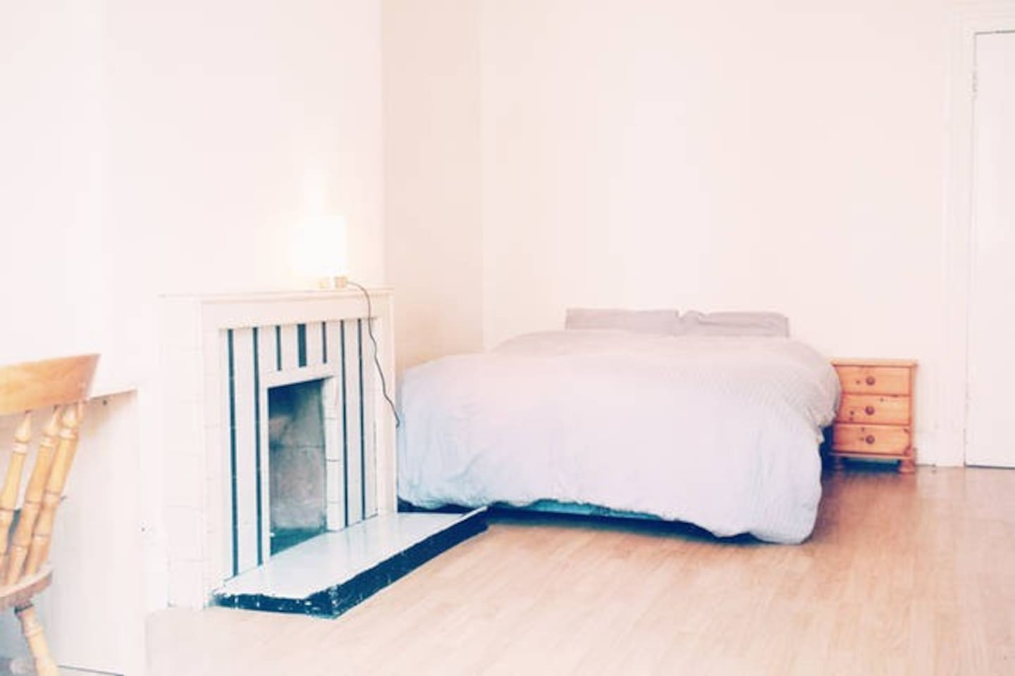 Bedroom with double bed, high celling, night stand, parquet flooring, gas heating