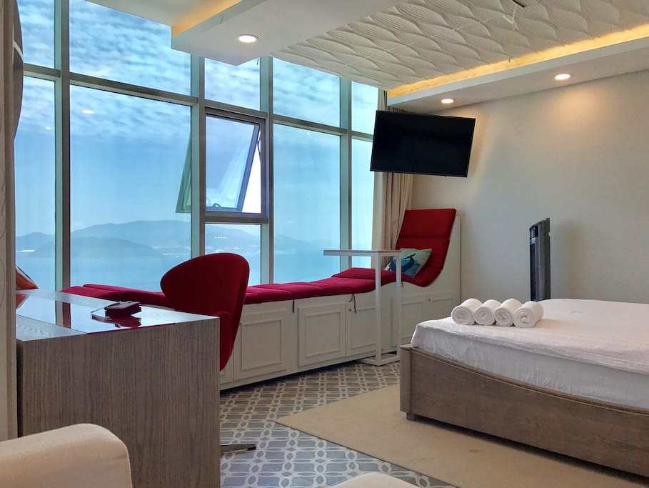 A panoramic sea-view through front window: queen-size bed, working table, TV with many English speaking channels and bench.