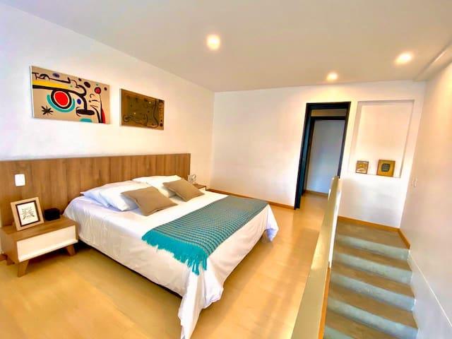Moderna habitación con cama queen. al fondo entrada al vestier y baño del segundo piso.