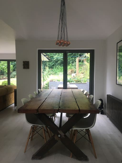 Hand made 10 seater dining table, in open plan living area, 12ft high ceilings with skylights. Large bifold doors leading to a hardwood decked entertainment area, with outside dining table, bordered by tall bamboo  This area has a fire pit, looks onto the pond and south facing private garden