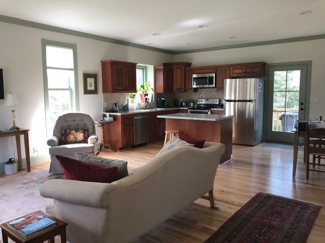 Your living room and kitchen with table, island, TV and internet, oriental rugs and hickory floors.