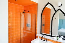 The orange bathroom compliments the blue room well!