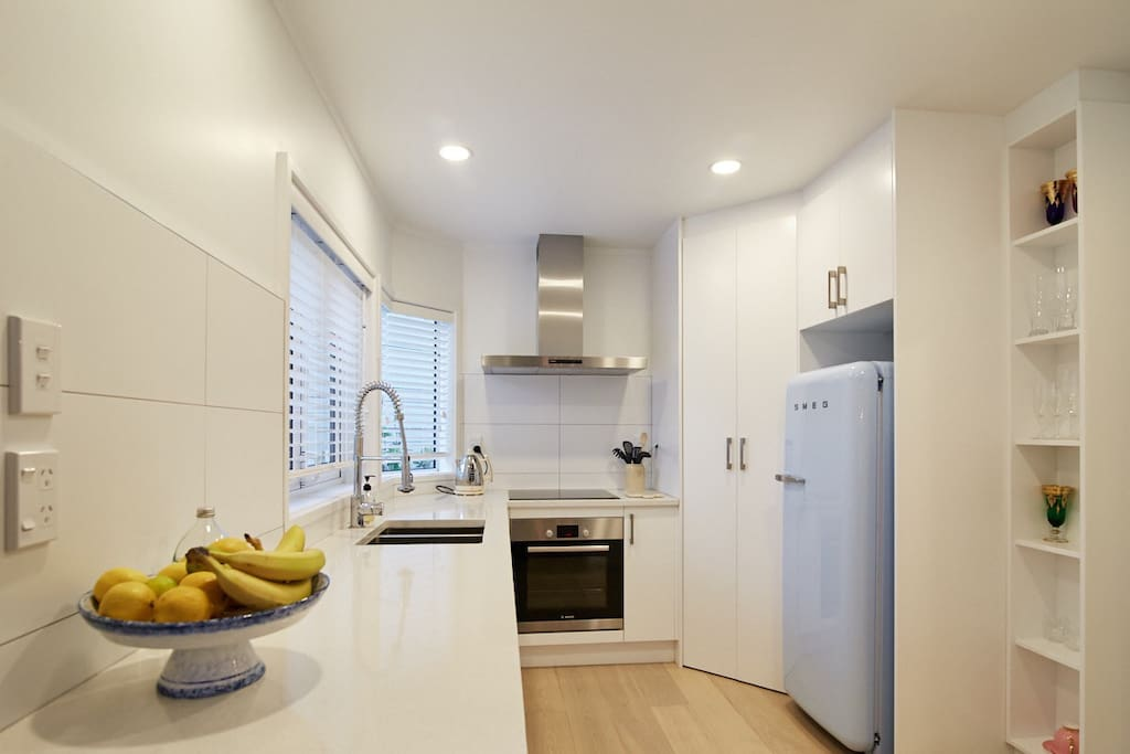 Kitchen with dishwasher, induction top cooker, well equipped with pots pans plates glasses. Tea and coffee