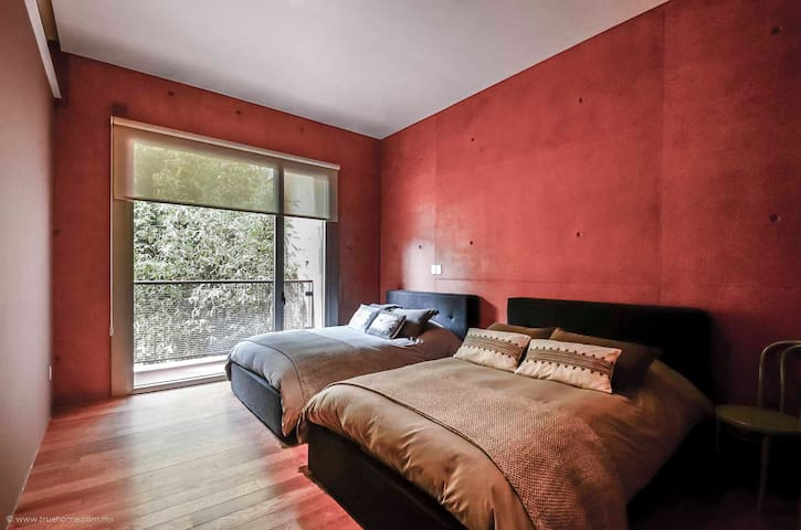 Large room with two double beds overlooking the building's lush gardens