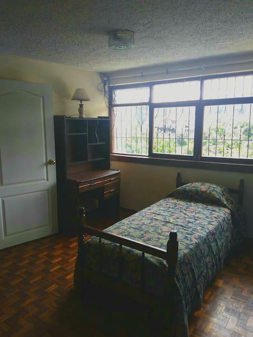 Dormitorio con cama de una plaza, escritorio y clóset