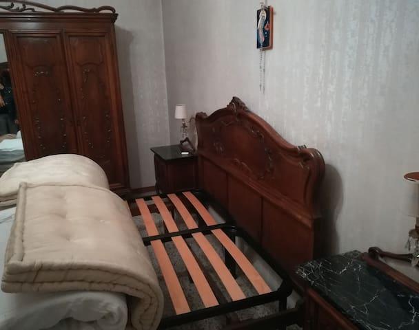 Dettaglio della camera da letto: mobili in stile barocco piemontese, reti del letto a doghe, materassi doppi.
