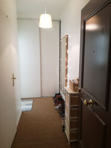 L'entrée avec interphone, un espace pour vos chaussures et manteau dans la penderie. La porte sur la gauche donne accès à la salle de bain