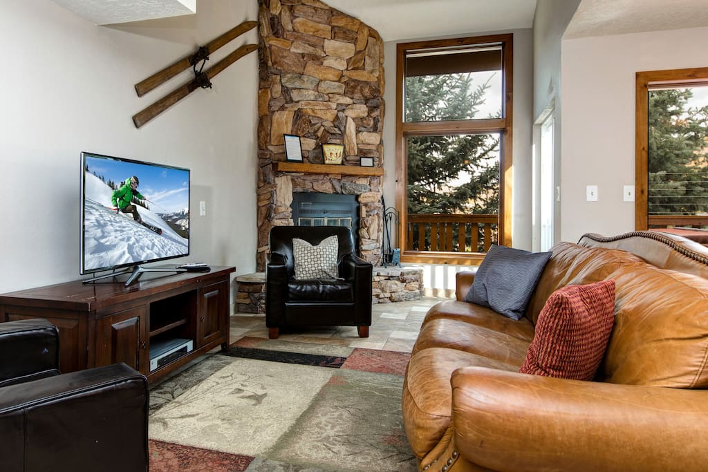 """A 42"""" TV and DVD player face the leather couches"""